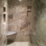 Custom shower with modern fixtures and granite seating